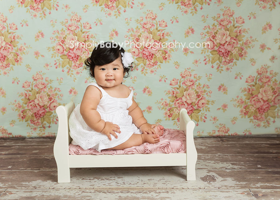 Baby posing on vintage bed