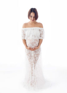 Maternity portrait of expecting mother in white lace gown